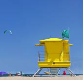 Yellow Life Guard Tower at the beach with people, kite surfer and blue sky — Stock Photo