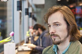 Portrait of a pensive and handsome young man in coffee shop — Stock Photo
