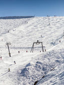 Skiing people, the chair lifts and rope tow systems of Zell am See ski region in Austria — Foto de Stock
