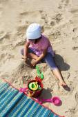 Child playing with sand at the beach — Stock Photo