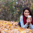 Fashionable woman with coffee lying down on fall leaves — Stock Photo #58296447