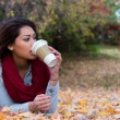 Stylish woman drinking coffee while lying down on autumn leaves — Stock Photo #58296507