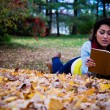 Young woman reading a book lying down on autumn leaves in the fa — Stock Photo #58296523
