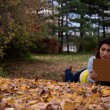 Young woman reading a book lying down on autumn leaves in the fa — Stock Photo #58296531