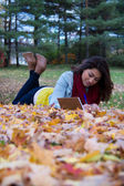 Girl writing in notebook while lying down on colorful autumn lea — Stockfoto