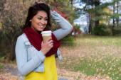 Woman enjoying a beverage on an autumn day — Stock Photo