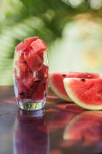 Watermelon pieces and slices in a glass on a dark table in Vietnam — Stock Photo