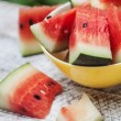 Watermelon pieces in a yellow plate on a white wooden table — Stock Photo #53012555