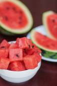 Watermelon pieces and slices in two plates on a dark wooden tabl — Stock Photo