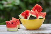 Watermelon pieces in a yellow plate on a white wooden table — Stock Photo