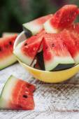 Watermelon pieces in a yellow plate on a white wooden table — 图库照片