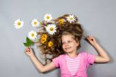 Girl lying with flowers in her hair — Stock Photo