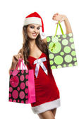 Girl with Christmas shopping in the hat of Santa Claus — Stock Photo