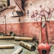 Red industrial fire extinguisher in an abandoned factory — Stock Photo #55265947
