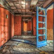 Blue door in red dilapdated corridor at an abandoned hotel — Stock Photo #70137815