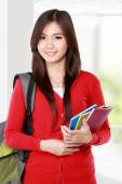 Beautiful female student with books smiling — Stock Photo
