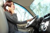 Young woman talking on the phone while driving — Stock Photo