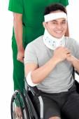 Injured young man in wheelchair help by nurse — Stock Photo