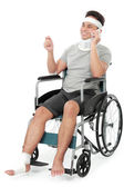 Injured young man in wheelchair talking on the phone — Stock Photo