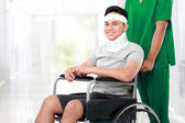 Nurse pushing young patient in wheelchair — Stock Photo