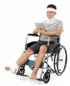 Injured young man in wheelchair play gadget — Stock Photo