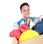 Box full of goodies carried by young man — Stock Photo