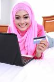 Young muslim woman work using laptop and holding a credit card — Stock fotografie