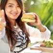 Young woman having lunch and give thumbs up for delicious food — Stock Photo #67362067