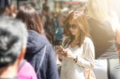 Woman using mobile phone in the crowd — Stock Photo