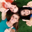Group girls lying on the grass showing thumb up — Stock Photo #69281537
