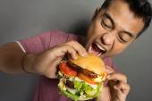 Young Man have a great desire to eat a burger — Stock Photo