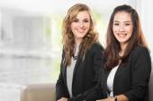 Two young businesswoman sitting next to each other, smile — Stock Photo