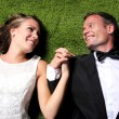 Newlywed couple lying on the grass and holding each other hands — Stock Photo #71709349
