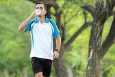 Junger sportlicher Mann zu Fuß, während ein Mineralwasser trinken — Stockfoto