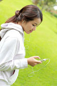 Sporty woman listening music from her smartphone — Stock fotografie