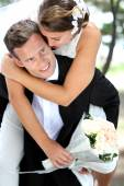 Groom pickaback his bride — Stock Photo