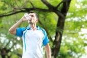 Young sporty man drinking mineral water — Stock Photo