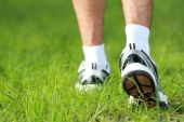 Human feet in running shoes to step on the grass — Stock Photo