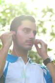 Sporty young man adjusting his earphone during jogging — Stock Photo