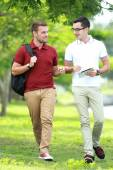 Two college students  studying together while walking and lookin — Stock Photo