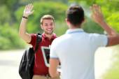 College student meet his friend and waving his hand — Stock Photo