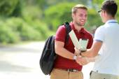 A college student happy to meet his friend and then shake hands — Stock Photo