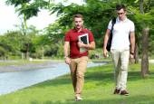 Two college students walking together at riverside — Stock Photo