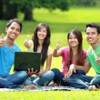 Students studying in the park using laptop computer. thumb up a — Stock Photo #76837591