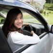 Happy young asian woman riding a car — Stock Photo #76840071