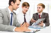 Три бизнесмены обсуждают новый план в офисе — Стоковое фото