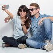 Mixed couple sitting on the floor taking self camera together — Stock Photo #78530124