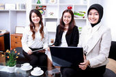 Three young businesswomen smiling while meeting — Stock Photo