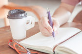 Woman writing on notepaper — Stock Photo