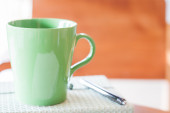 Closeup green mug with pen and notebook — Photo
